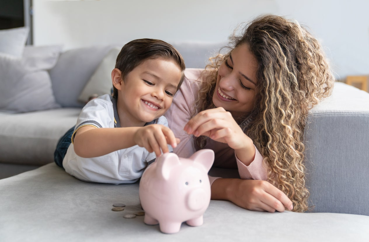 mother and son putting money in a piggybank