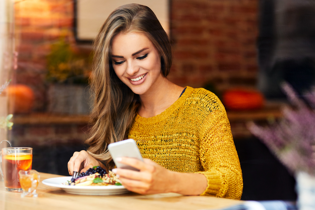 woman looking at phone while sitting and eating in a cafe